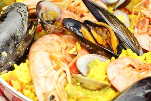 Closeup of seafood paella with mussels, clams and king prawns